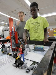 Coach Michael Stromberg watches Tipler Middle School student Olufunsho Akinleye of the Polystyrenes work on the different obstacles their robot will maneuver around the course. The team is getting ready for the state FIRST LEGO competition.