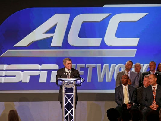 Commissioner John Swofford, center, announces an ACC/ESPN Network during a news conference at the Atlantic Coast Conference Football Kickoff in Charlotte, N.C., Thursday, July 21, 2016. (AP Photo/Chuck Burton)