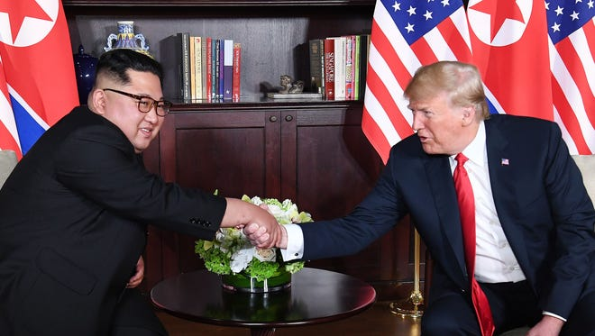 President Trump shakes hands with North Korean leader Kim Jong Un as they sit down for their summit at the Capella Hotel on Sentosa island in Singapore Tuesday.