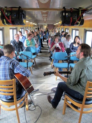 In this Saturday Nov. 7, 2015 photo, the Meadows Brothers, Dustin, left, and Ian, entertain passengers on the Roots on the Rails music train during its first East Coast Trip between Bellows Falls and Rutland, Vt. About 50 passengers spent the day listening to music while riding in vintage rail cars of the Green Mountain Express rolling through the countryside. (AP Photo/Wilson Ring)
