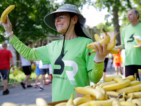 Volunteers pass out bananas to Bellin Run finishers