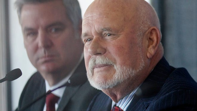 Whalers owner Peter Karmanos Jr. talks about the sale of the team. Behind him is Mike Vellucci.