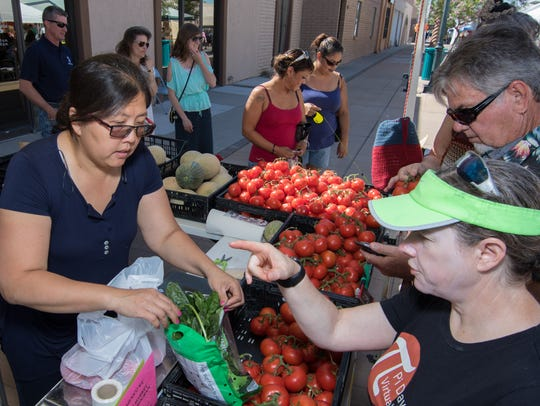 Customers purchase fresh produce at the Perfect Produce