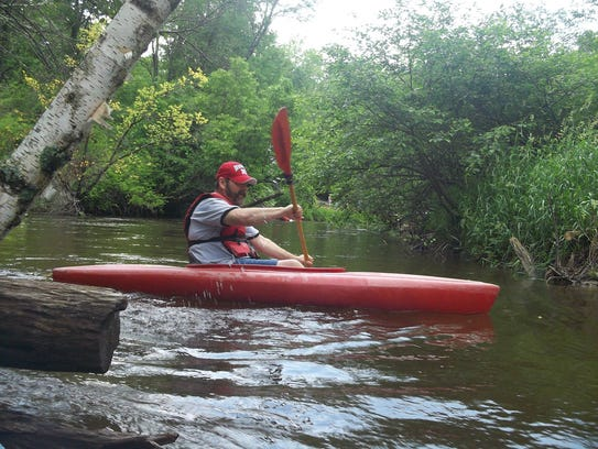 A kayaker moves down the Pine River.