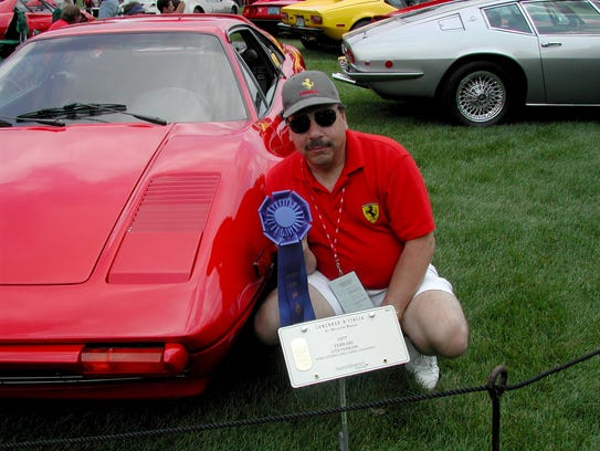 In 2004, John Ottino is photographed with a 1977 Ferrari