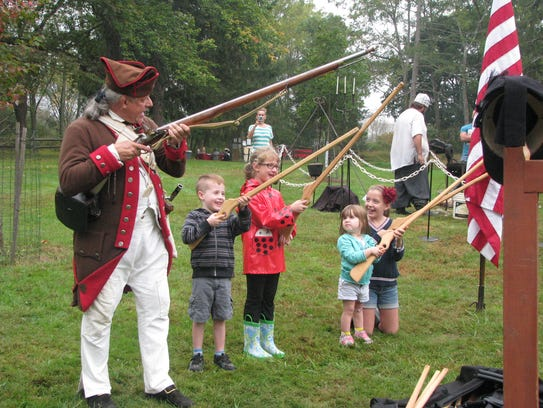 Children conducting a musket drill with wood muskets