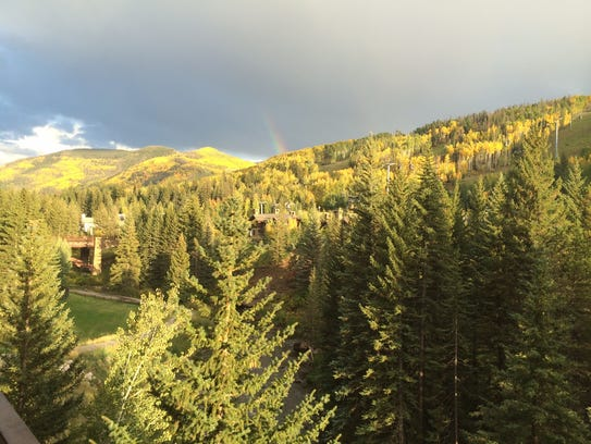 A rainbow above autumn gold, seen from a balcony at