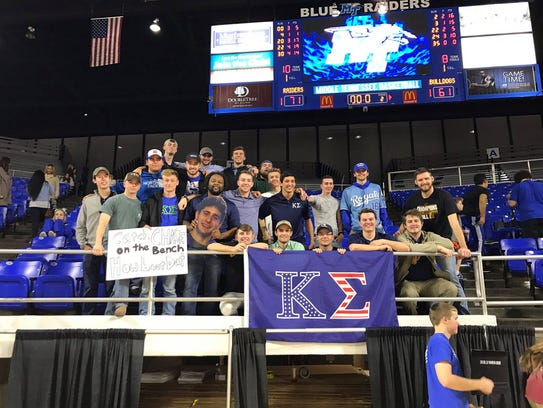 Members of the Kappa Sigma fraternity hold a sign and