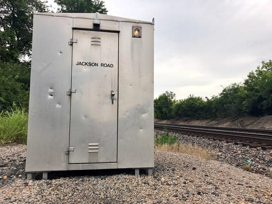 This railroad crossing signal box, dented from bullets,