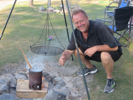 Ron Savage tends to the grill while camping.