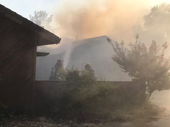Redding firefighters try to knock down a fire at one