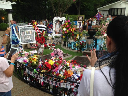 Mourners and fans gather at Elvis Presley's grave at