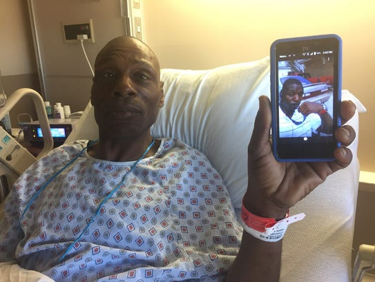 Roc Peeler holds up a selfie photo of himself from