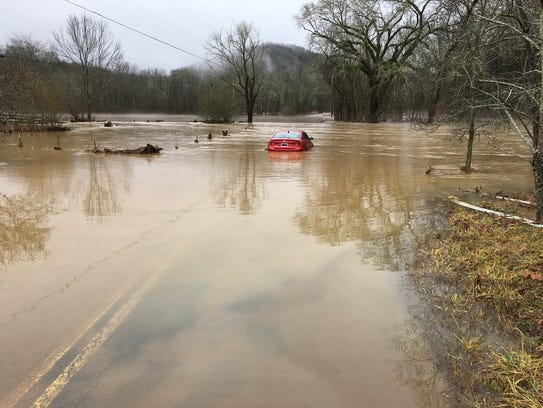 A car is trapped in high waters on Mountain Road in