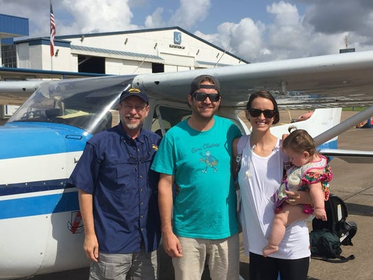 Pilot Mark Blair (left) with Patient Avery Benjamin (infant) and parents Christopher and Abbey Benjamin.