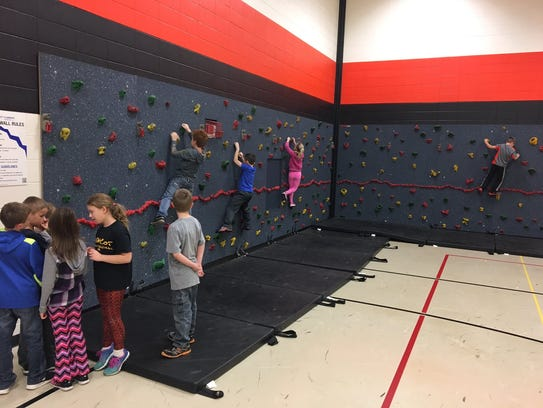 Third-graders climb a rock wall at O.H. Schultz Elementary