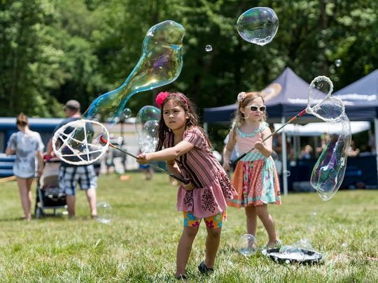 The ice cream festival includes lots of activities for kids, like the bubble making done by Isabel Oberly (left), 7, and Melanie Mintz, 6, at the 2017 festival.