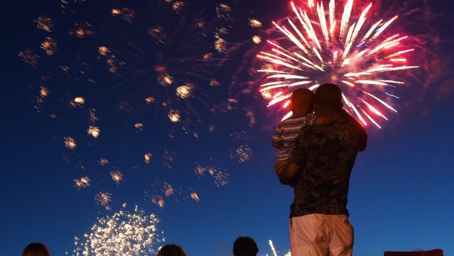 Spectators watch Sioux Falls Jaycees Fourth Of July fireworks from the bike path near the W.H. Lyon Fairgrounds.