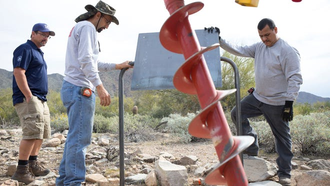 Esteban Gonzalez (center) and Carlos Arenas (right) position a nature trail sign, March 18, 2015, that will be installed on the Kovach Family Trail off of the Lost Dog Wash Trailhead, 12601 N. 124th Street, Scottsdale. Assisting in the positioning is City of Scottsdale preserve planner Scott Hamilton (left).