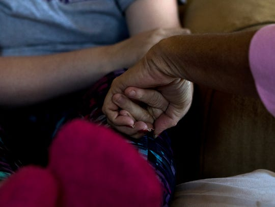 Cody Goodrich, left, holds hands with her mother Lorie