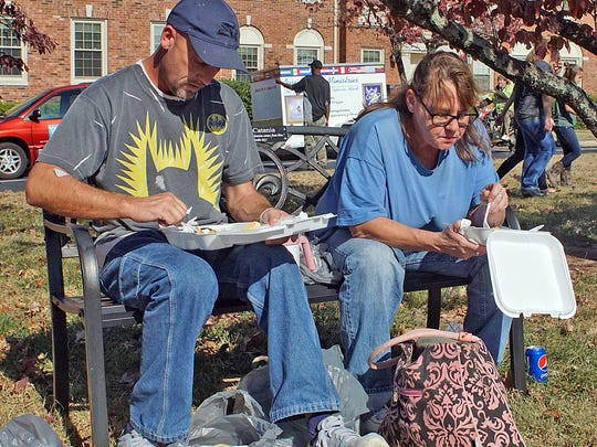 Friends John Montgomery, left, and Hope Tomlinson  enjoy their Thanksgiving meals on a bench outside the church instead of dining in. Montgomery said he had just been released from the hospital and was very thankful for the meal.