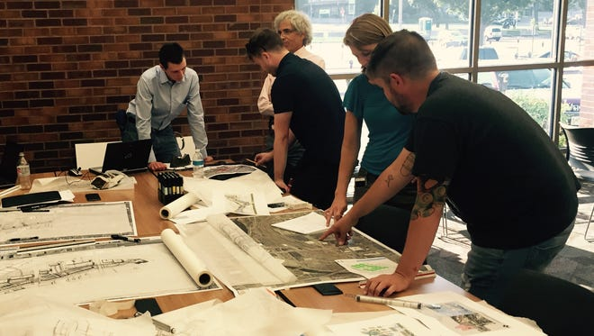 Officials with RDG Design and Planning discuss potential ideas for a downtown railyard redevelopment project with members of the public Wednesday evening during an open house at the downtown library.