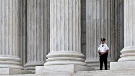 In this Oct. 7 photo, a police officer is dwarfed amid the marble columns of the Supreme Court in Washington.
