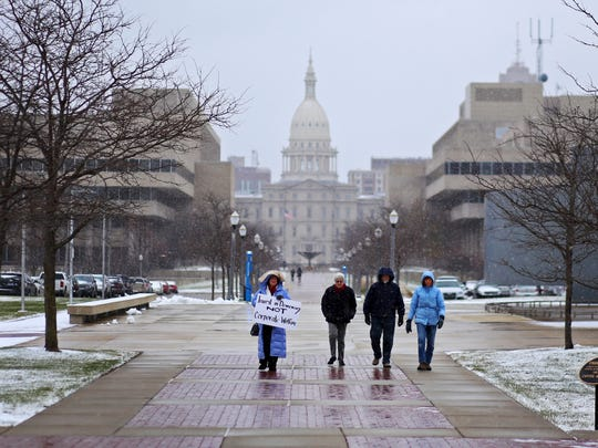 Michigan residents walk towards the Michigan State Supreme Court for a rally to speak out against the court's decision to shut down Michigan's recount on Thursday.
