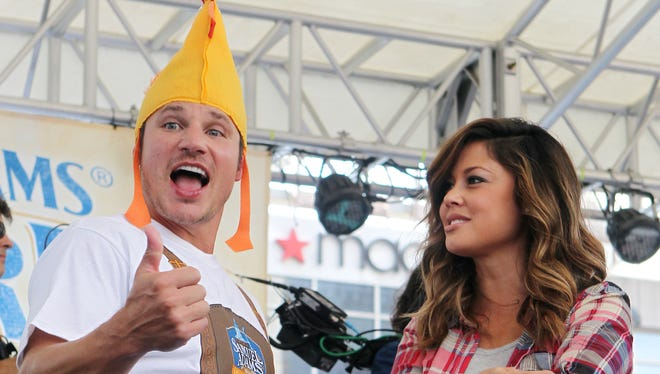 """Nick Lachey, with his wife, Vanessa, gives the thumbs up to fans after leading the """"Chicken Dance"""" at Oktoberfest Zinzinnati in 2014."""
