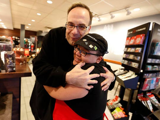 In this Dec. 19, 2016 photo, Father Jim Sichko is embraced by employee Victoria Lovejoy after giving her a $100 bill to at Starbucks in Lexington, Ky.  Sichko paid out about $6,000 in holiday good will to a Starbucks counter crew, a Muslim refugee family, a Hispanic family with a desperately ill father and an LGBT man who needed help with groceries for himself and his mother. (Charles Bertram/Lexington Herald-Leader via AP)