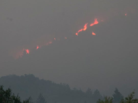 Flames burn along a ridge above Sonoma, Calif., Oct.