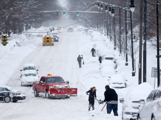People dig out vehicles after overnight snow in Albany, N.Y., on Feb. 14. Schools are closed across a swath of eastern New York from the mid-Hudson Valley to the Albany area.