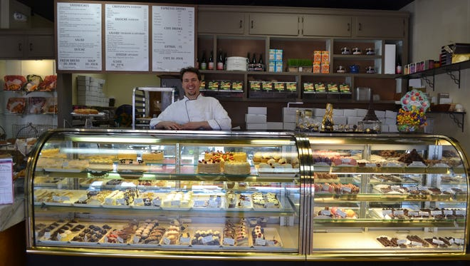 Au Péché Mignon co-owner Joseph Gans poses in front of an assortment of French treats