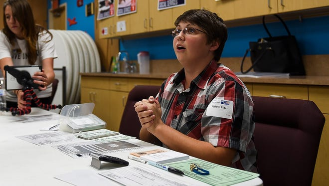 JoBeth Rider helps run a booth in a community-wide poverty simulation hosted by the Coloradoan with United Way of Larimer County Thursday, Sept. 18, 2015, in Fort Collins, CO. The simulation is designed to give people a taste of what it is like to live in poverty for a month.