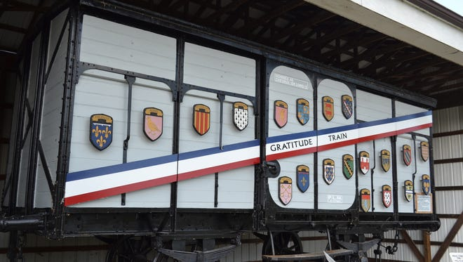 "This Ohio boxcar, located at Camp Perry, was one of 49 ""forty-and-eights"" that comprised the Merci Train, which was sent to America by the French people as a token of gratitude for America's humanitarian aid in the aftermath of World War II. The train was filled with 250 tons of gifts. The plaques on the front represent the coats of arms of French provinces."