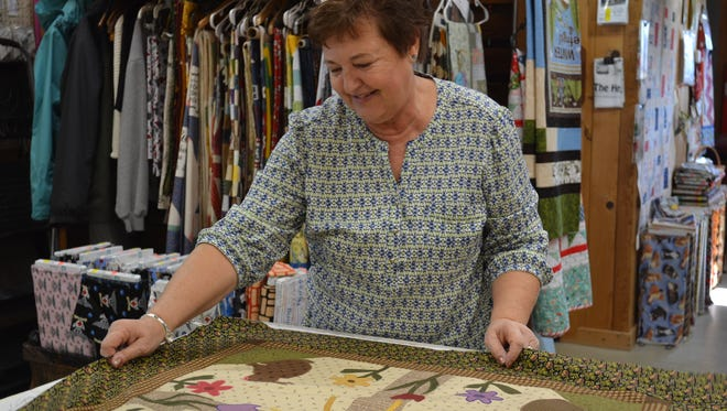Employee Sandi Wood works on a quilt at The Door Mouse. Although the shop no longer offers quilting classes, the staff is always happy to help customers choose fabric and offer advice on quilting problems.