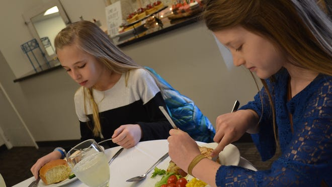 Like all the students, Cora Liskai, left, and Elise Miller used  three forks while eating their semi-formal luncheon at Down Thyme Café.