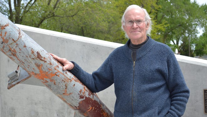 James Havens stands beside his sculpture at the Public Safety Service Memorial in Gibsonburg, which features a 36-foot, 7,000-pound section of the Main Antenna Mast from the North Tower of the World Trade Center.