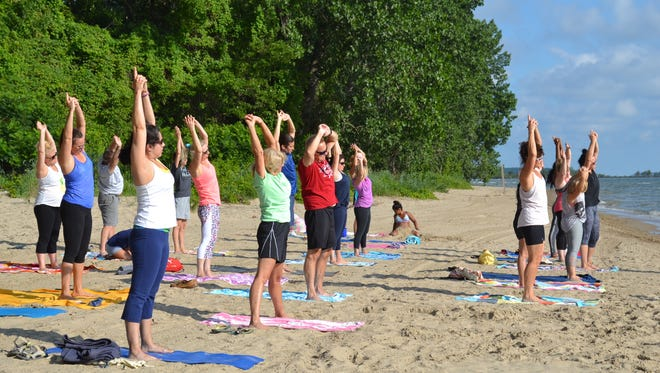 Students stretch in Donna Lueke's Yoga on the Beach class while the daughter of a student plays in the sand nearby. Lueke said children are always welcome at the classes, whether they participate or just play nearby.