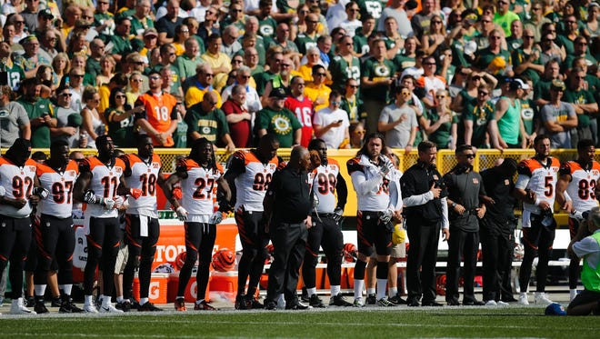 Bengals link arms during the national anthem.