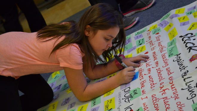 Kyrstin Porter signs her name to a kindness banner that will hang in the hallway of Clyde Elementary School.