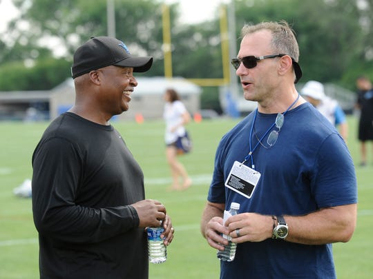 Chris Spielman chats with Lions coach Jim Caldwell at training camp on Sunday.