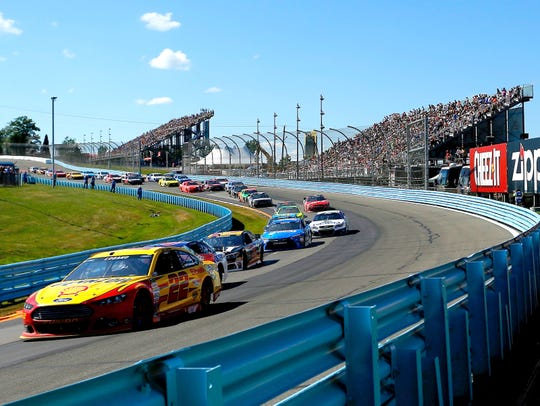 Joey Logano leads a pack of cars past the filled Turn