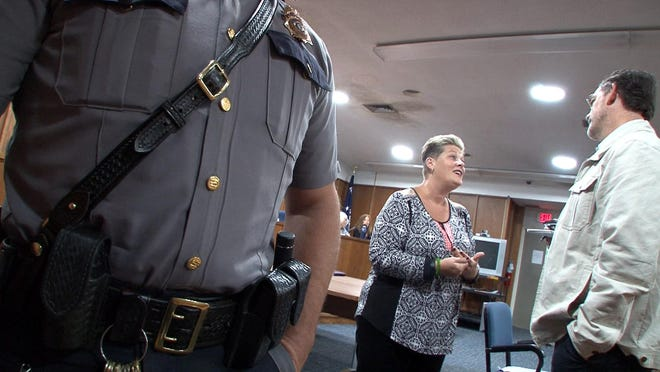 A police officer escorts an Asbury Park Press photographer from the Manchester town hall room where a tax lien auction was about to start. The Press was improperly barred from photographing the public event. Reporter Shannon Mullen (right) speaks with Manchester Township Court Administrator Tracy Barcus during the Oct. 6 dispute.