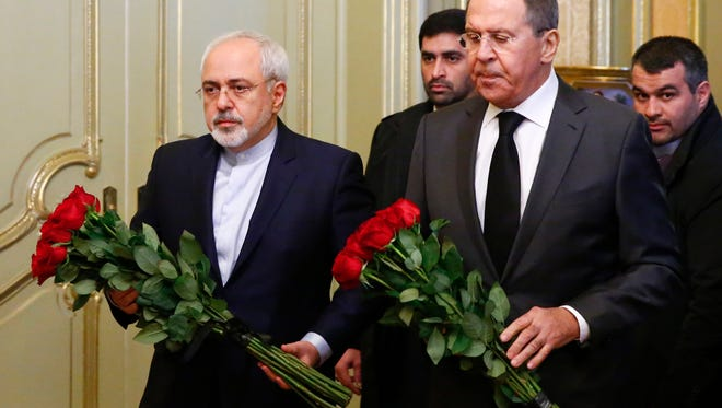 Russian Foreign Minister Sergey Lavrov, second right, and his Iranian Foreign Minister Mohammad Javad Zarif attend a ceremony in memory of murdered Russian ambassador to Turkey Andrei Karlov before their talks in Moscow, Russia, Dec. 20, 2016.