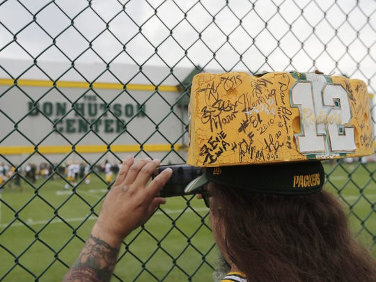 A fan with a cheesehead covered in autographs takes photos of the Green Bay Packers practice at minicamp on Tuesday.