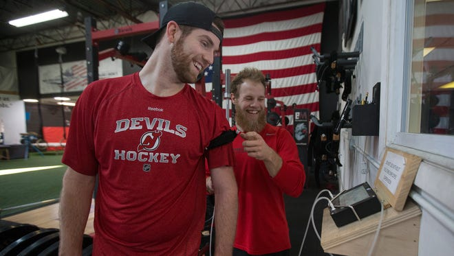 New Jersey Devils goalie Scott Wedgewood (left) and Barwis Methods trainer Nick Montoni share a laugh during a recent workout in Plymouth.
