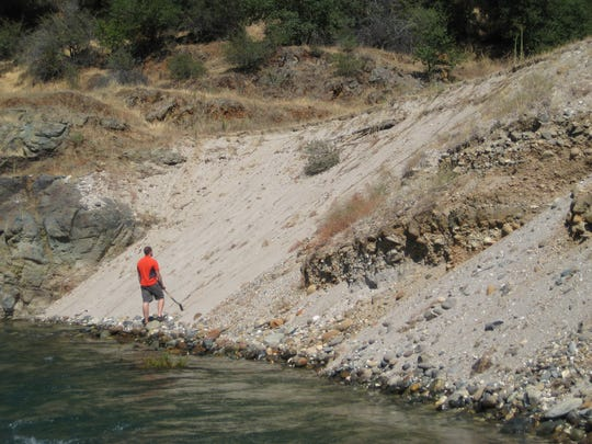 A man stands in front of a mercury-laced earthen terrace alongside California's Yuba River, downstream of several massive gold mines. The next big flood is likely to wash mercury-laden sediment into the river and to the valley below.