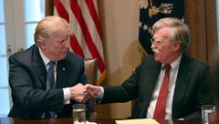 President Trump, left, shakes hands with national security