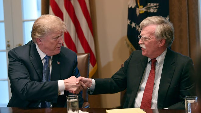 President Trump, left, shakes hands with national security adviser John Bolton in the Cabinet Room of the White House on Monday, April 9, 2018, at the start of a meeting with military leaders.